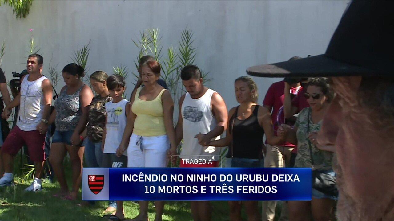 Familiares e amigos fazem roda de oração na porta do Ninho do Urubu