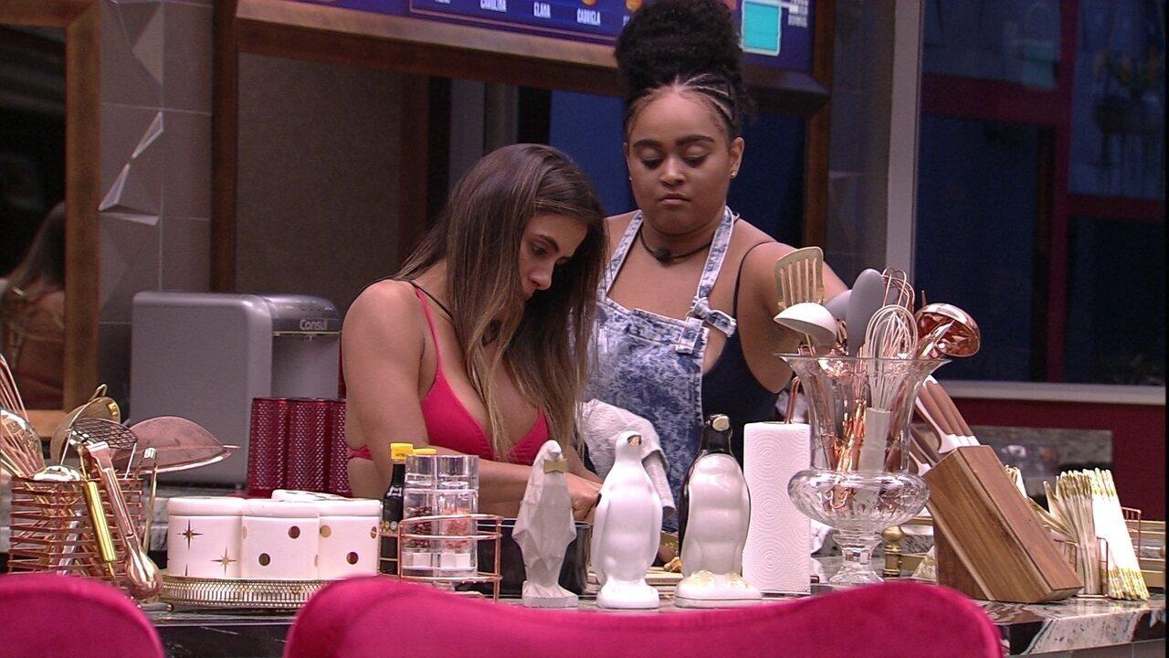 Rízia e Carolina arrumam a cozinha em silêncio