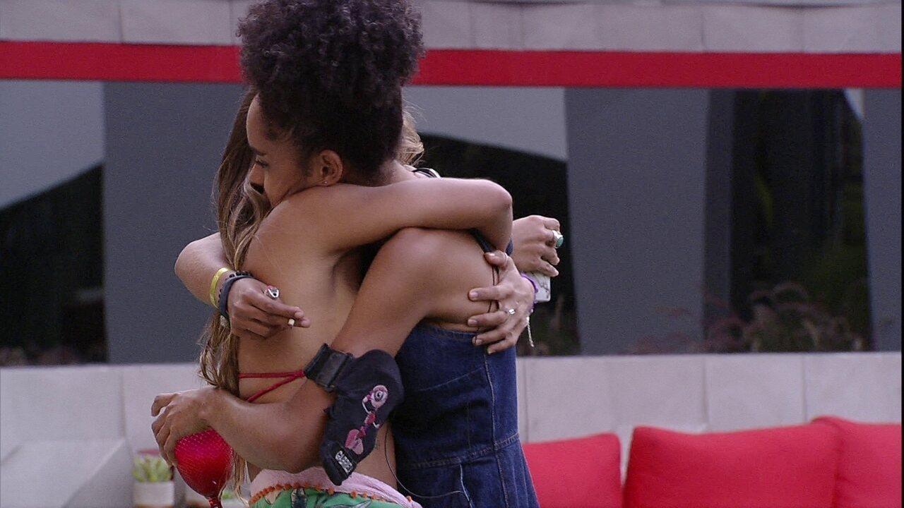 Gabriela abraça e beija Carolina no jardim