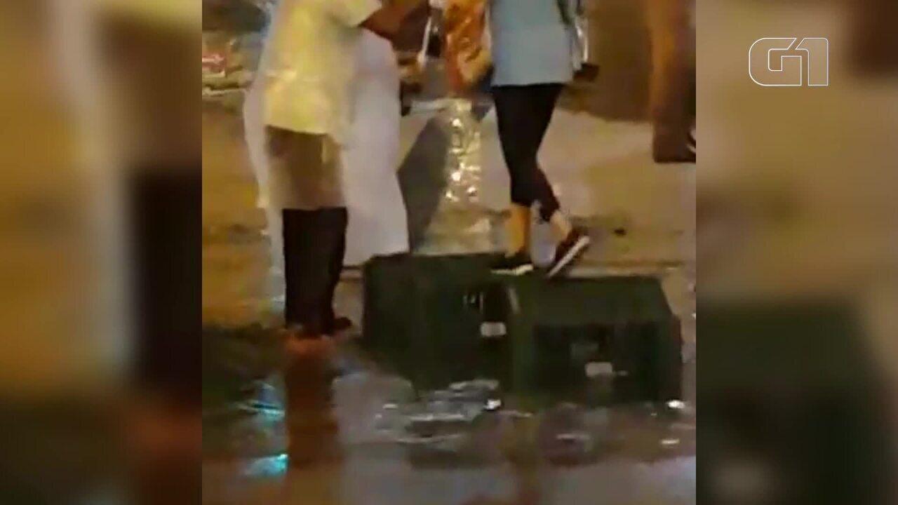 Vídeo mostra homem ajudando idosa a atravessar a rua durante temporal