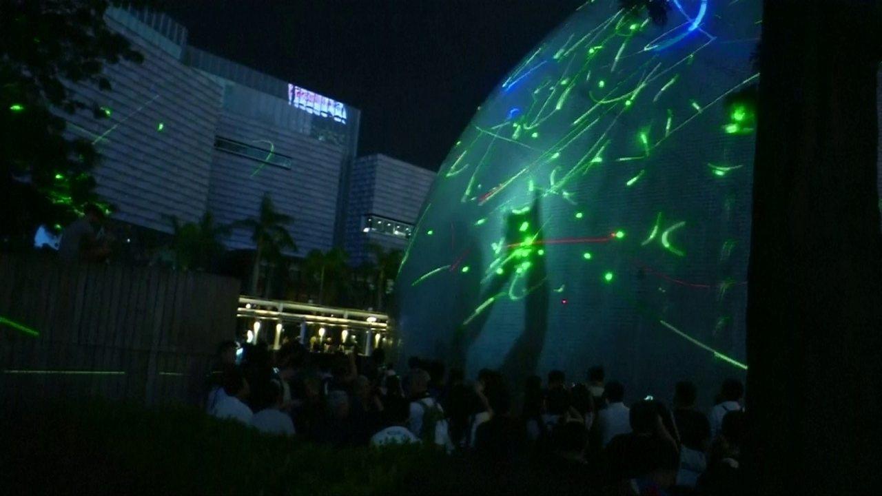 Manifestantes usam canetas com laser para iluminar o Museu Espacial de Hong Kong