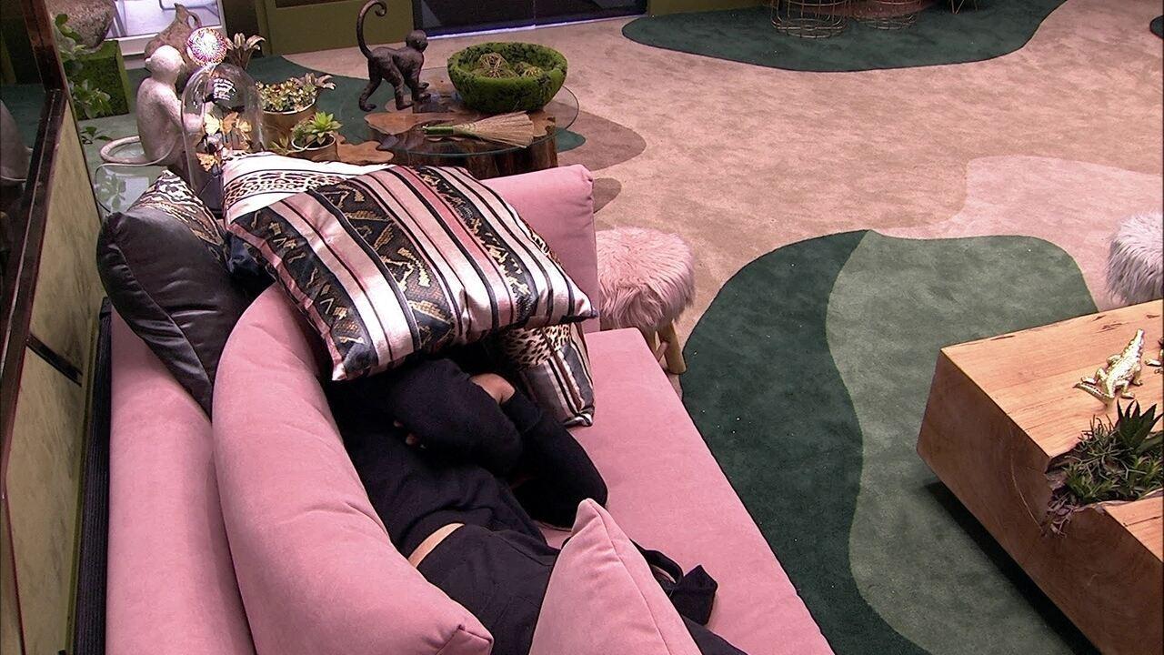 Chumbo deita no sofá da sala e cobre o rosto com almofadas