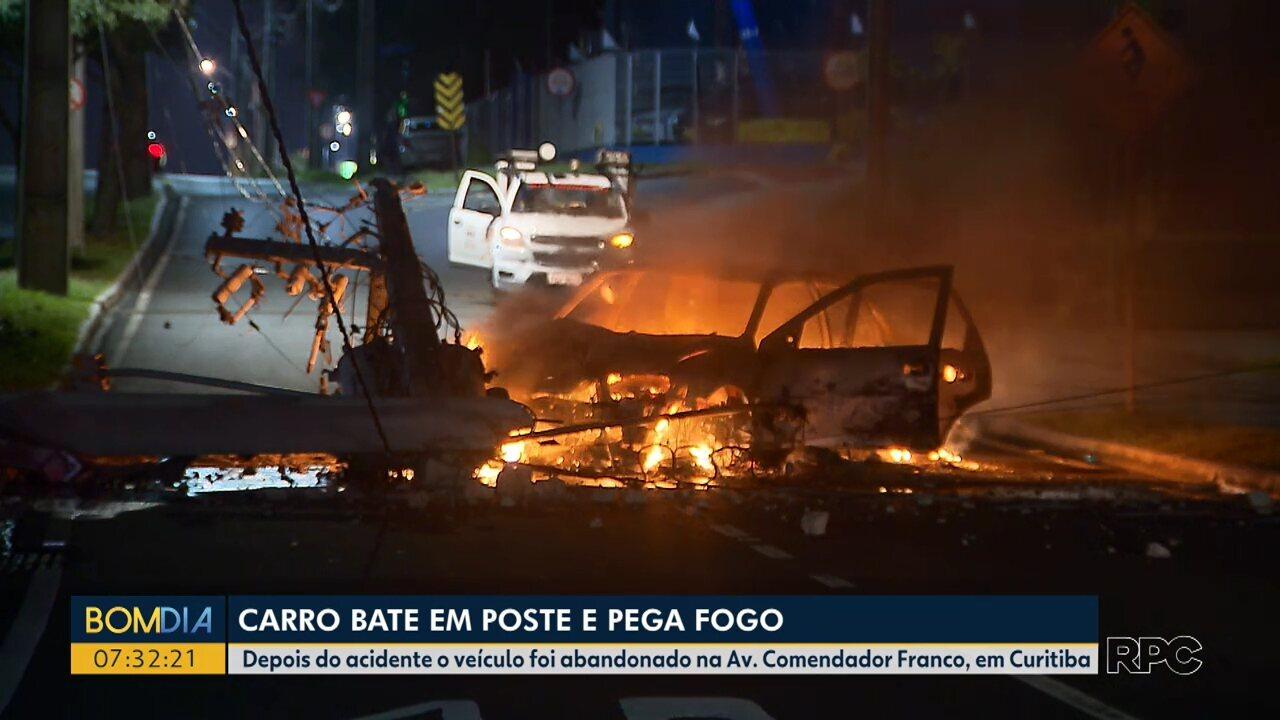 Carro pega fogo após bater em poste